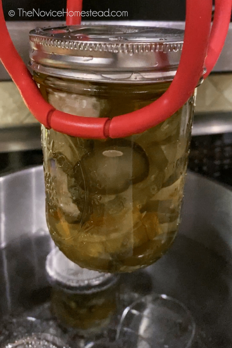 using canning tongs to remove jar of pickles from pot of hot water