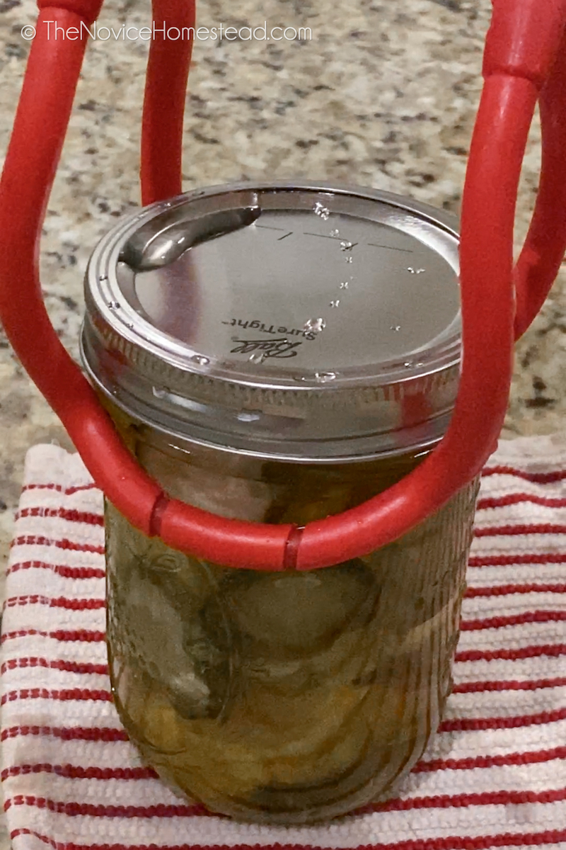 placing jar of pickles on counter with tongs