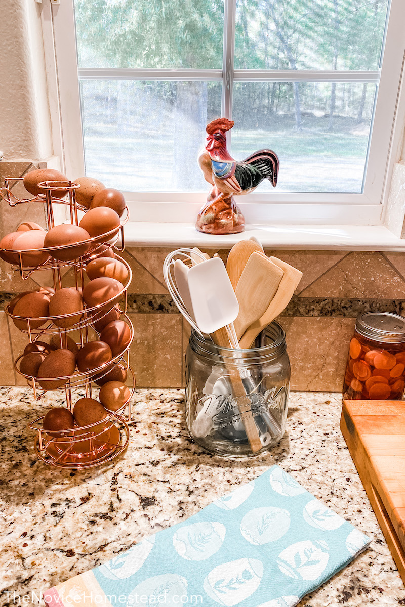 countertop with farmhouse style spiral egg holder and mason jar with cooking utensils